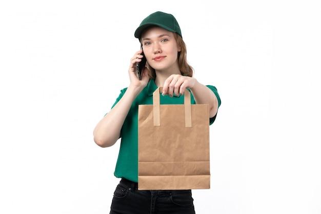 Widok z przodu młoda kobieta kurier w zielonym mundurze, uśmiechając się trzymając pakiet i rozmawia przez telefon
