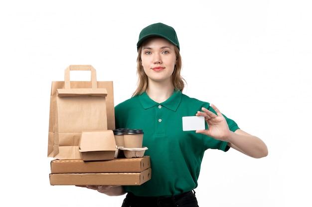 Widok z przodu młoda kobieta kurier w zielonym mundurze uśmiechnięta trzymając białą kartę i paczki dostawy żywności