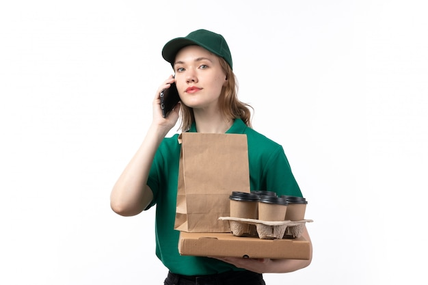 Widok z przodu młoda kobieta kurier w zielonym mundurze uśmiechnięta trzymając filiżanki kawy opakowania żywności rozmawia przez telefon