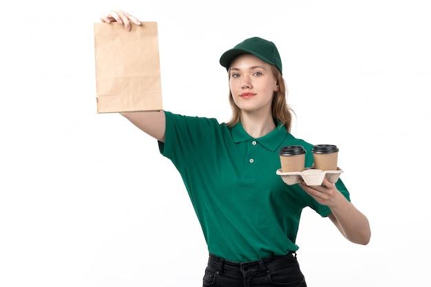 Widok z przodu młoda kobieta kurier w zielonym mundurze uśmiechnięty trzymając filiżanki i opakowanie