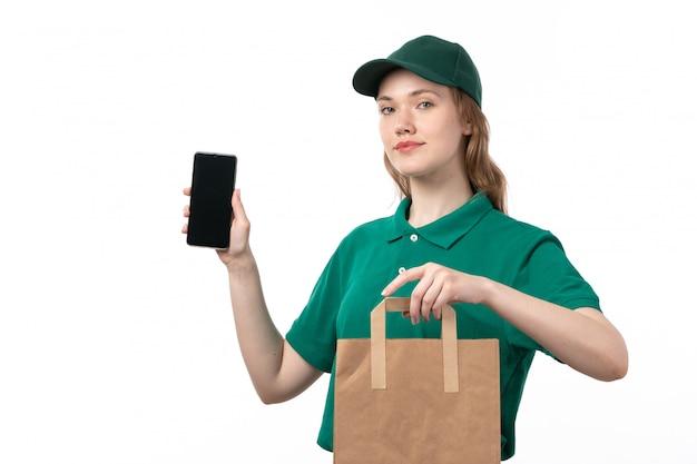 Widok z przodu młoda kobieta kurier w zielonym mundurze uśmiechnięty trzymając smartfon i opakowanie żywności