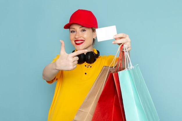 Widok z przodu młoda kobieta kurier w żółtej koszuli i czerwonej pelerynie posiadającej pomnożenie i zakupy pakietów na niebieskiej przestrzeni