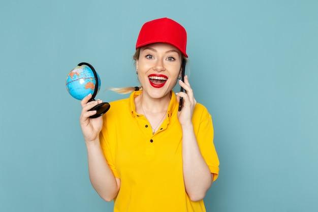 Widok z przodu młoda kobieta kurier w żółtej koszuli i czerwonej pelerynie rozmawia przez telefon uśmiecha się na niebieskiej przestrzeni