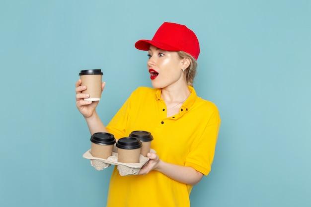 Widok z przodu młoda kobieta kurier w żółtej koszuli i czerwonej pelerynie trzyma filiżanki kawy na niebieskiej pracy kosmicznej