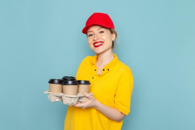 Widok z przodu młoda kobieta kurier w żółtej koszuli i czerwonej pelerynie trzyma filiżanki kawy na niebieskim pracowniku kosmicznym