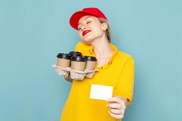 Widok z przodu młoda kobieta kurier w żółtej koszuli i czerwonej pelerynie trzyma plastikowe kubki do kawy białą kartkę z uśmiechem na niebieskiej przestrzeni