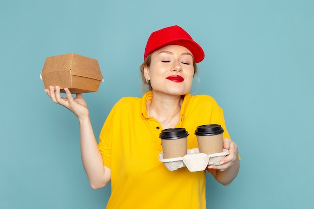 Widok z przodu młoda kobieta kurier w żółtej koszuli i czerwonej pelerynie trzyma plastikowe kubki do kawy i pakiet żywności na niebieskiej przestrzeni