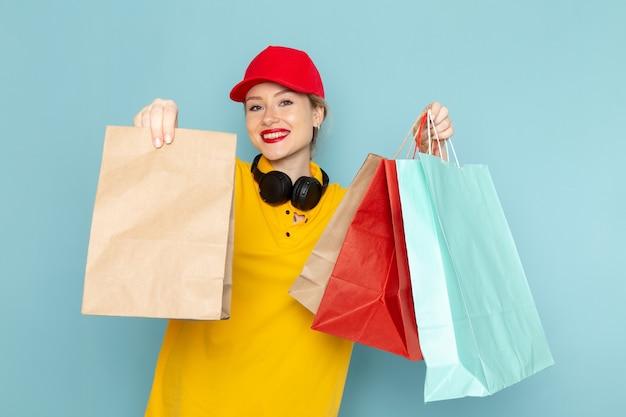 Widok z przodu młoda kobieta kurier w żółtej koszuli i czerwonej pelerynie, trzymając pomnóż i zakupy pakiety na niebieskiej przestrzeni