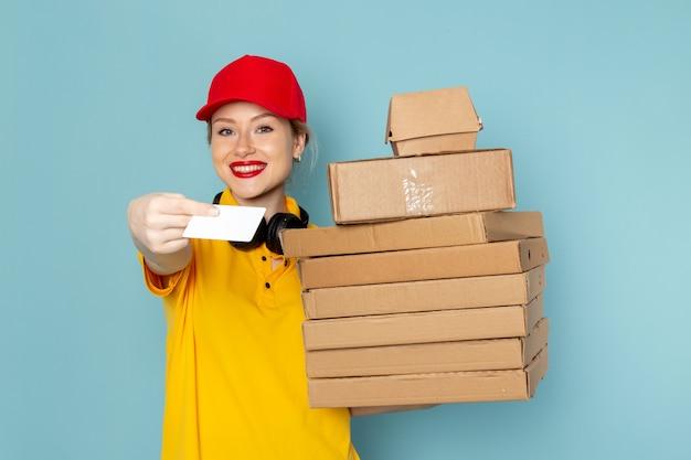Widok z przodu młoda kobieta kurier w żółtej koszuli i czerwonej pelerynie, trzymając pomnóż pakiety i białą kartę na niebieskiej kosmicznej pracy
