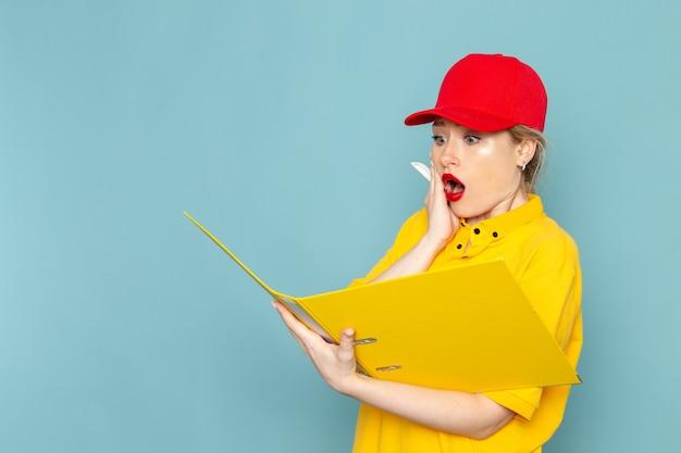 Widok z przodu młoda kobieta kurier w żółtej koszuli i czerwonej pelerynie, trzymając żółty plik zapisując notatki na temat emocji pracownika niebieskiej przestrzeni