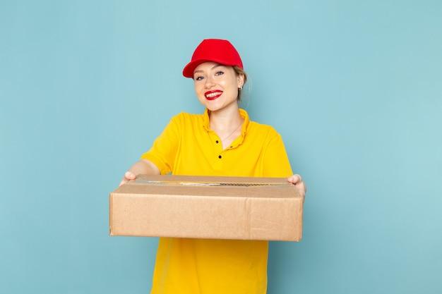 Widok z przodu młoda kobieta kurier w żółtej koszuli i czerwonej pelerynie, uśmiechając się i dając pakiet na niebieskiej pracy kosmicznej