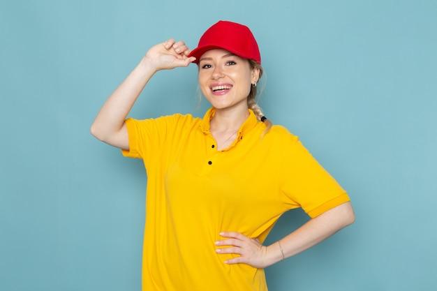 Widok z przodu młoda kobieta kurier w żółtej koszuli i czerwonej pelerynie, uśmiechając się i pozując na niebieskiej przestrzeni pracy dziewczyna