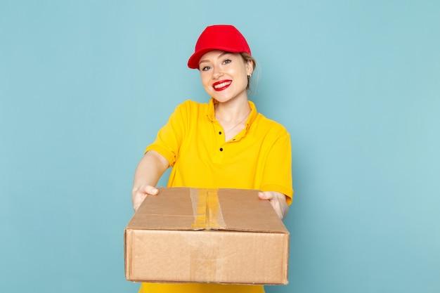 Widok z przodu młoda kobieta kurier w żółtej koszuli i czerwonej pelerynie, uśmiechając się i trzymając pakiet na niebieskiej pracy kosmicznej