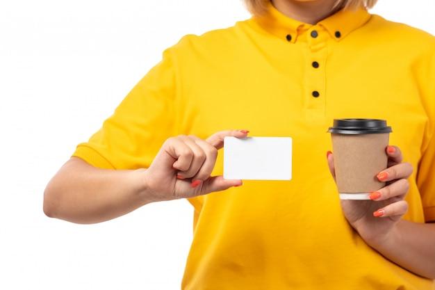 Widok z przodu młoda kobieta kurier w żółtej koszuli, trzymając białą kartę i filiżankę kawy