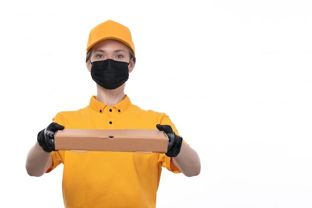 Widok z przodu młoda kobieta kurier w żółtych jednolitych czarnych rękawiczkach i czarnej masce trzyma pudełko na żywność