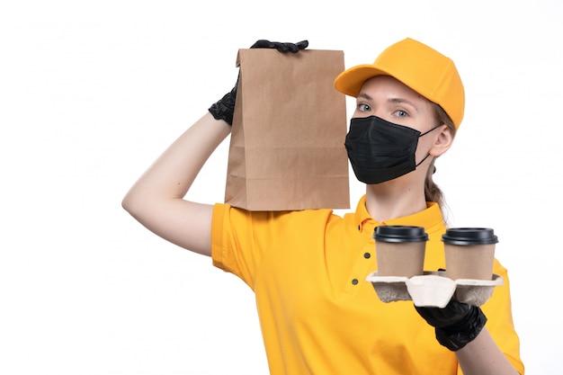 Widok z przodu młoda kobieta kurier w żółtych jednolitych czarnych rękawiczkach i czarnej masce trzymającej opakowanie żywności i filiżanki