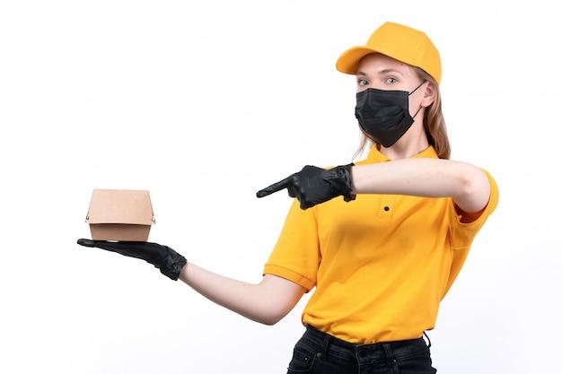 Widok z przodu młoda kobieta kurier w żółtych jednolitych czarnych rękawiczkach i czarnej masce trzymającej opakowanie żywności