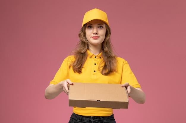 Widok z przodu młoda kobieta kurier w żółtym mundurze gospodarstwa pudełko z dostawą żywności świadczące usługi na różowym biurku jednolite stanowisko pracownika usługi dostawy