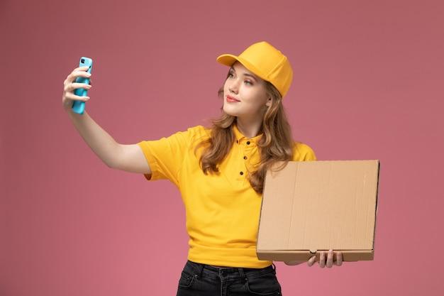 Widok z przodu młoda kobieta kurier w żółtym mundurze robi zdjęcie z pakietem żywności na różowym tle biurko jednolite stanowisko pracownika usługodawcy