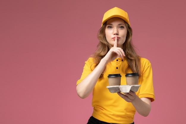 Widok z przodu młoda kobieta kurier w żółtym mundurze trzyma dostawę kawy pokazując znak ciszy na różowym biurku jednolity pracownik usługi dostawy