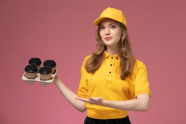 Widok z przodu młoda kobieta kurier w żółtym mundurze trzyma filiżanki kawy na różowym tle biurko jednolite stanowisko pracownika usługodawcy