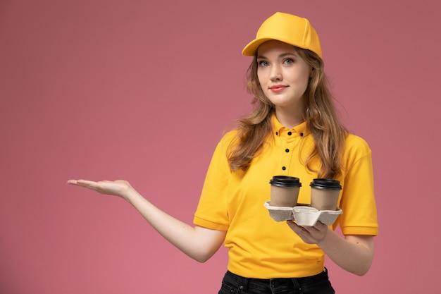 Widok z przodu młoda kobieta kurier w żółtym mundurze trzymając dostawę kawy pozowanie na różowym biurku jednolite stanowisko pracownika usługi dostawy