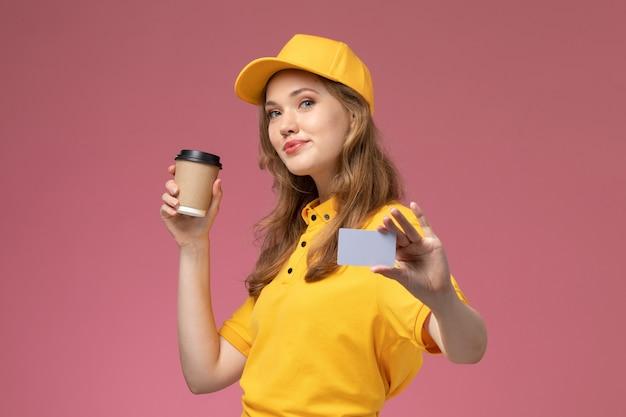 Widok z przodu młoda kobieta kurier w żółtym mundurze, trzymając filiżankę kawy i szarą kartkę na ciemnoróżowym biurku jednolita dostawa pracownik serwisu