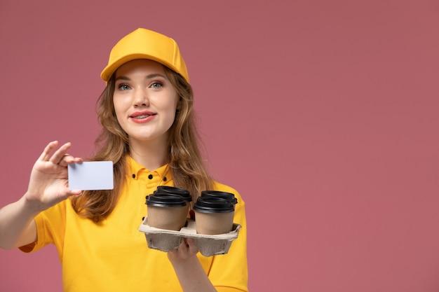 Widok z przodu młoda kobieta kurier w żółtym mundurze, trzymając filiżanki kawy z białą kartą na ciemnoróżowym biurku jednolita usługa dostawy pracownica
