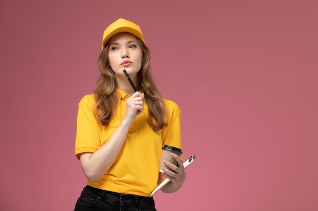 Widok z przodu młoda kobieta kurier w żółtym mundurze trzymając notatnik i kawę na ciemnoróżowym biurku jednolita usługa dostawy pracownica