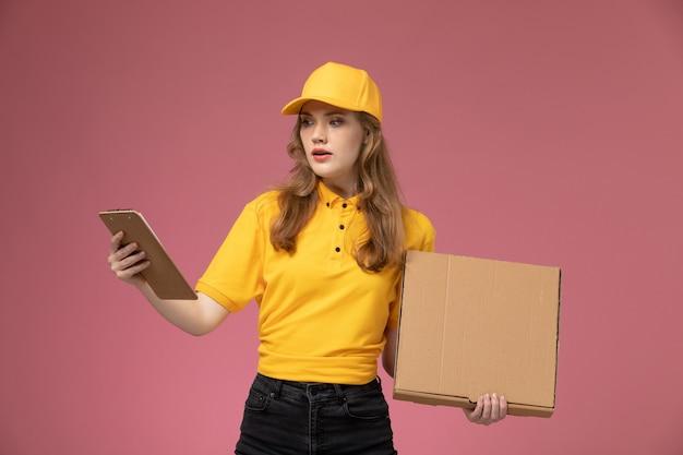 Widok z przodu młoda kobieta kurier w żółtym mundurze trzymając pakiet z jedzeniem i notatnikiem na różowym tle biurko jednolite stanowisko pracownika usługodawcy