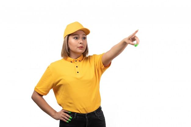 Widok z przodu młoda kobieta kurier w żółtym mundurze, wskazując w dal