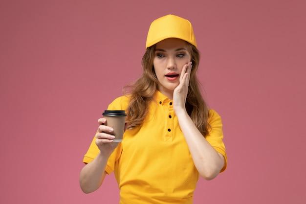 Widok z przodu młoda kobieta kurier w żółtym mundurze żółtej pelerynie trzymającej kawę na ciemnoróżowym tle jednolity kolor usługi dostawy
