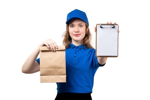Widok z przodu młoda kobieta kurier żeński pracownik usług dostawy żywności gospodarstwa notatnik i pakiet żywności uśmiecha się na białym tle
