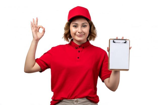 Widok z przodu młoda kobieta kurier żeński pracownik usług dostawy żywności posiadający notatnik dla podpisów uśmiecha się na białym tle