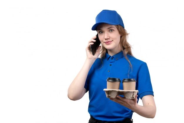Widok z przodu młoda kobieta kurier żeński pracownik usług dostawy żywności trzymając filiżanki kawy i rozmawia przez telefon uśmiecha się na białym tle