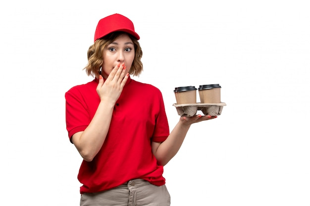 Widok z przodu młoda kobieta kurier żeński pracownik usług dostawy żywności trzymając filiżanki kawy z zaskoczony wyraz na białym tle