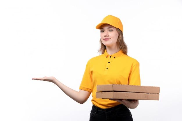 Widok z przodu młoda kobieta kurier żeński pracownik usług dostawy żywności trzymając pudełka po pizzy z uśmiechem na twarzy na białym tle
