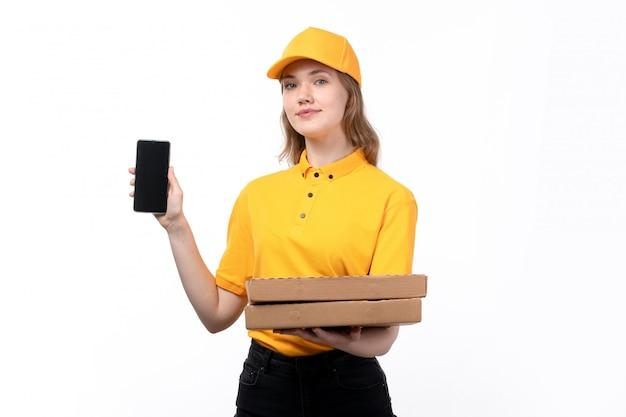 Widok z przodu młoda kobieta kurier żeński pracownik usług dostawy żywności, trzymając smartfon i pudełka po pizzy na białym tle