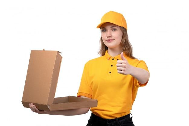 Widok z przodu młoda kobieta kurier żeński pracownik usług dostawy żywności uśmiecha się trzymając puste pudełko po pizzy na białym tle