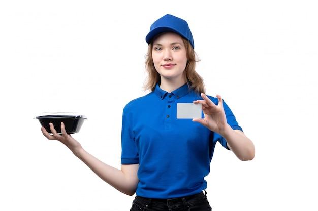 Widok z przodu młoda kobieta kurier żeński pracownik usług dostawy żywności uśmiechnięta trzymając miskę z jedzeniem i białą kartą na białym tle