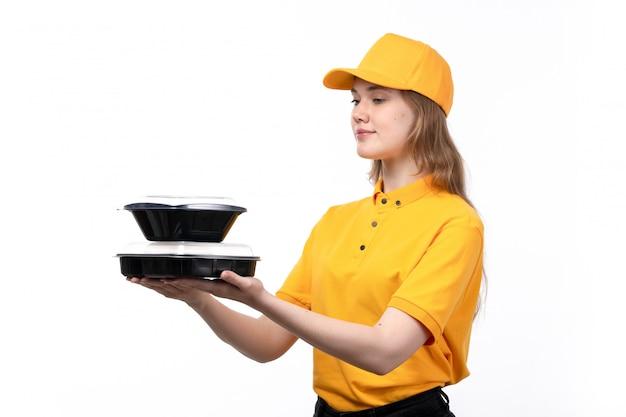 Widok z przodu młoda kobieta kurier żeński pracownik usług dostawy żywności uśmiechnięte gospodarstwa miski z jedzeniem na białym tle