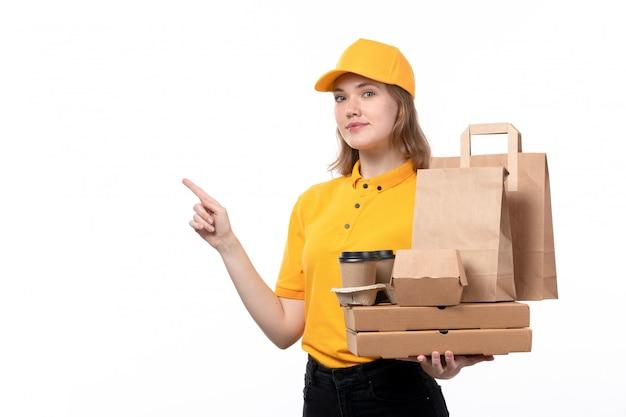 Widok z przodu młoda kobieta kurier żeński pracownik usługi dostawy żywności trzymając filiżanki i opakowania dostawy żywności na białym tle