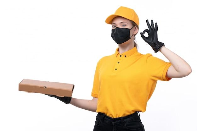 Widok z przodu młoda kobieta kurierka w żółtych, jednolitych czarnych rękawiczkach i czarnej masce trzymającej pudełko po pizzy pokazujące w porządku znak