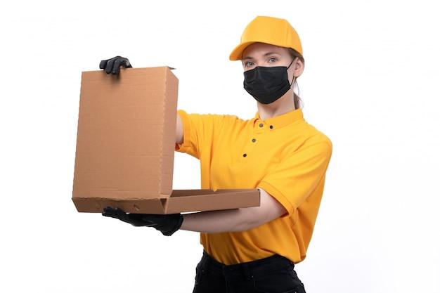 Widok z przodu młoda kobieta kurierka w żółtych mundurowych czarnych rękawiczkach i czarnej masce trzyma pudełko po pizzy otwierające go