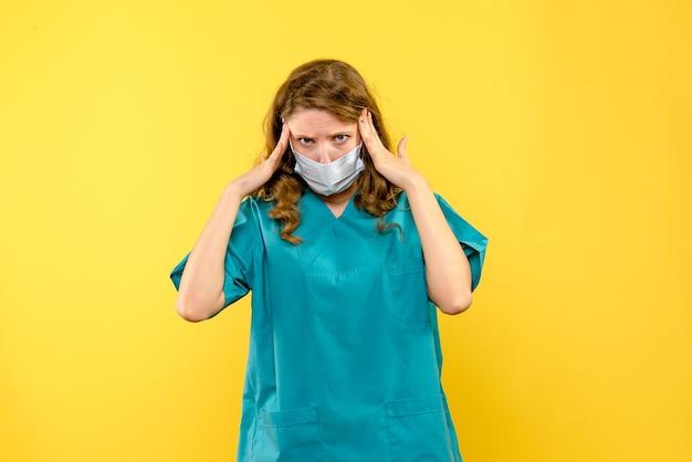 Widok z przodu młoda kobieta lekarz podkreślił na żółtej przestrzeni