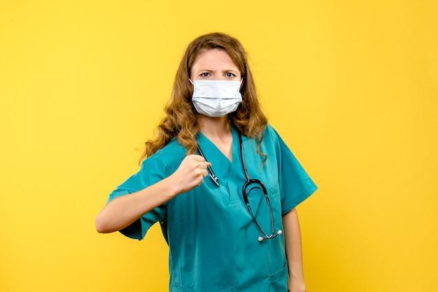 Widok z przodu młoda kobieta lekarz w masce na żółtej przestrzeni