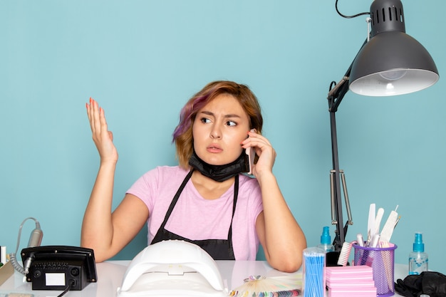 Widok z przodu młoda kobieta manicure w różowej koszulce z czarnymi rękawiczkami i czarną maską rozmawia przez telefon na niebiesko
