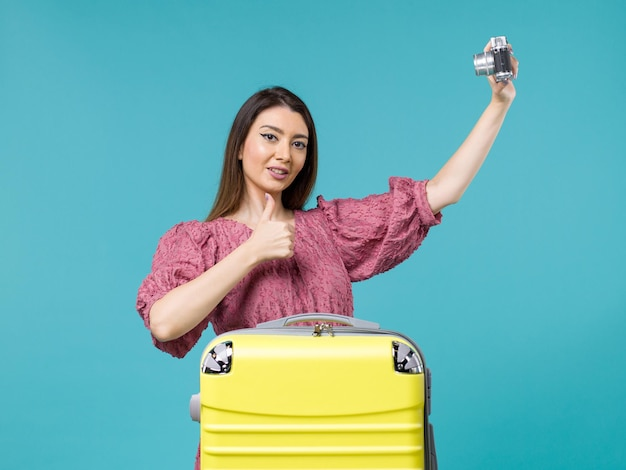 Widok z przodu młoda kobieta na wakacjach, biorąc zdjęcie z aparatem na niebieskim tle podróż kobieta za granicą wakacje morskie