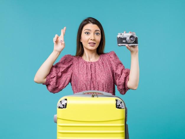 Widok z przodu młoda kobieta na wakacjach, biorąc zdjęcie z aparatem na niebieskim tle podróż wycieczka morska kobieta za granicą wakacje