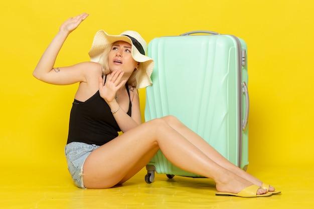 Widok z przodu młoda kobieta na wakacjach siedząca z zieloną torbą na żółtej ścianie kobieta podróż podróż słońce morze